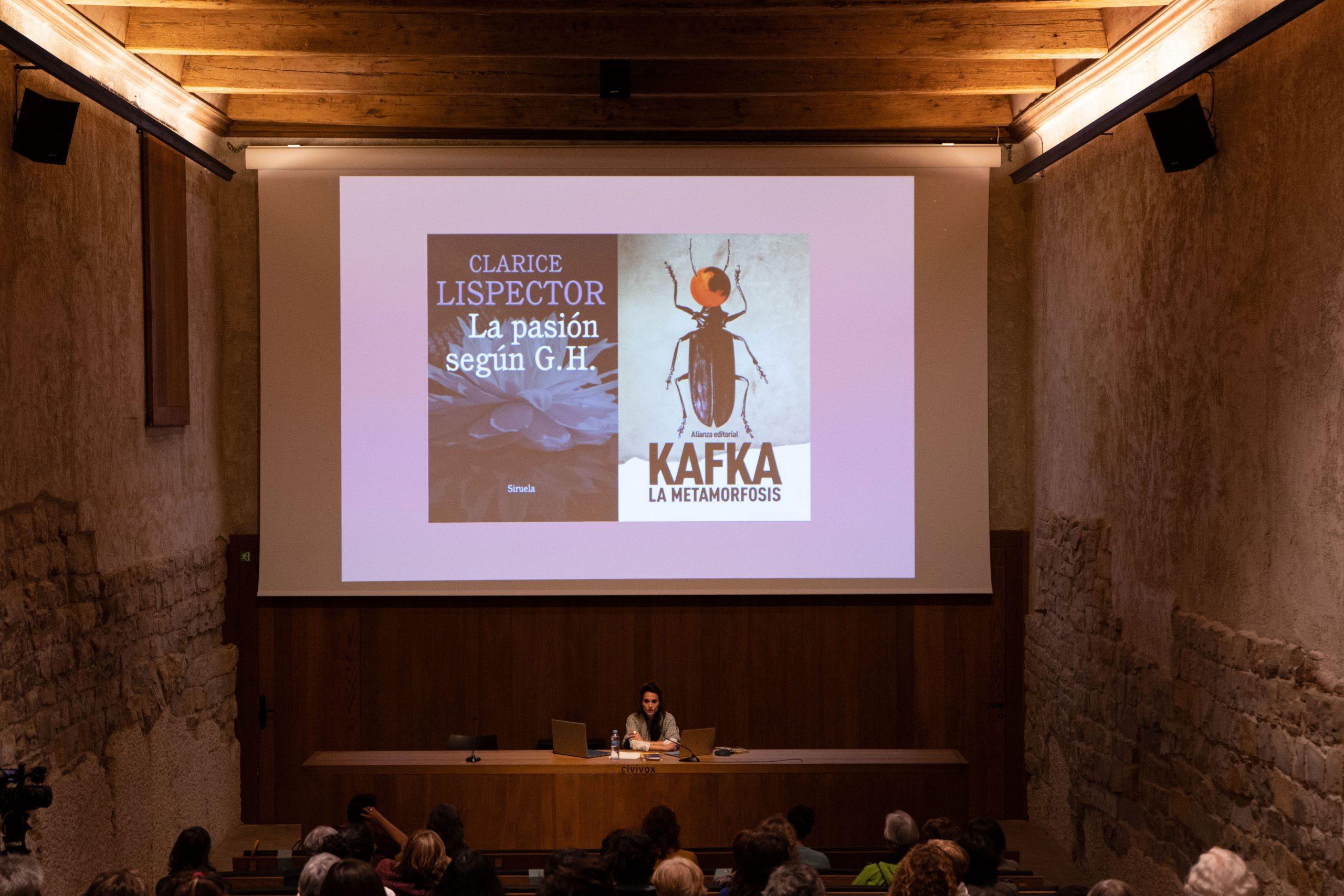 Plano general de una sala con la proyección de un libro de Clarice Lispector y Kafka y con Florencia del Campo en la mesa de ponencia.