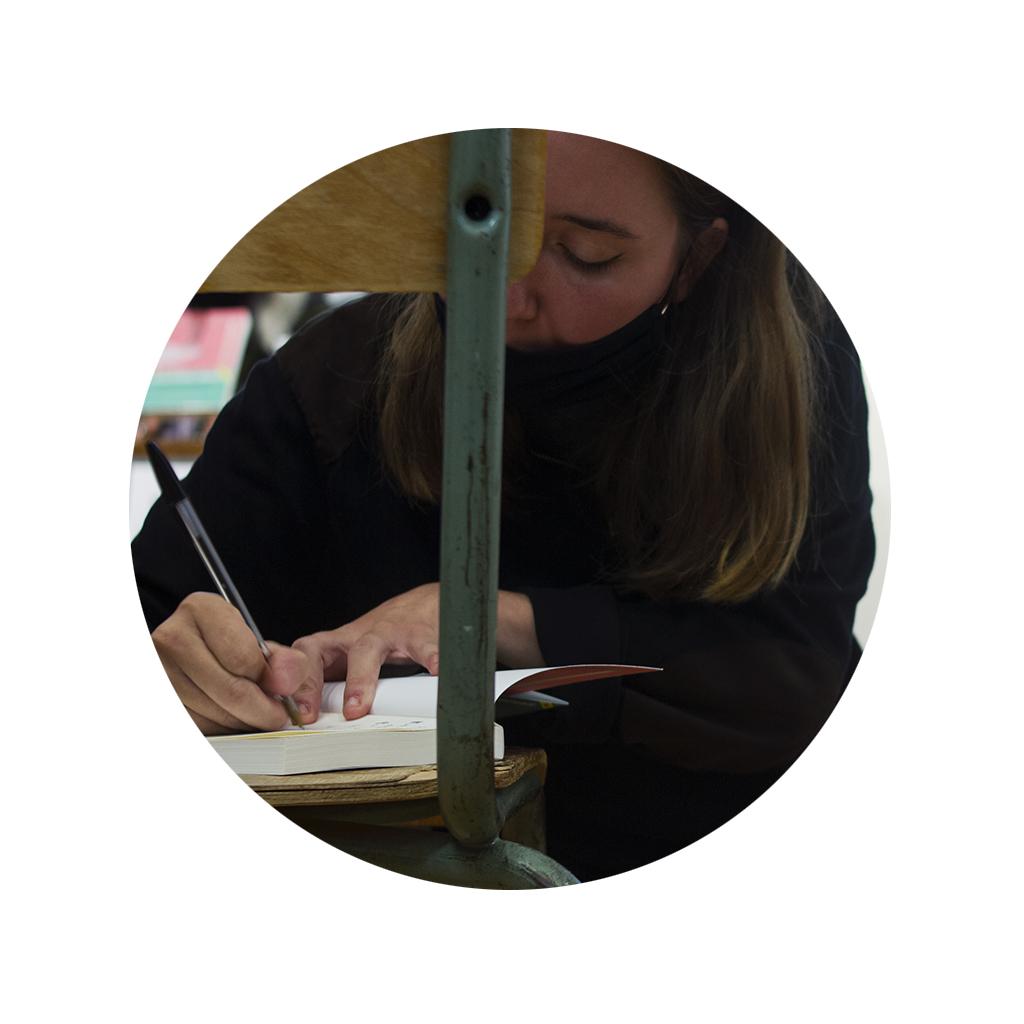 Anna Pacheco firmando un autógrafo sobre una silla en los Encuentros Letraheridas 2020 en Katakrak.