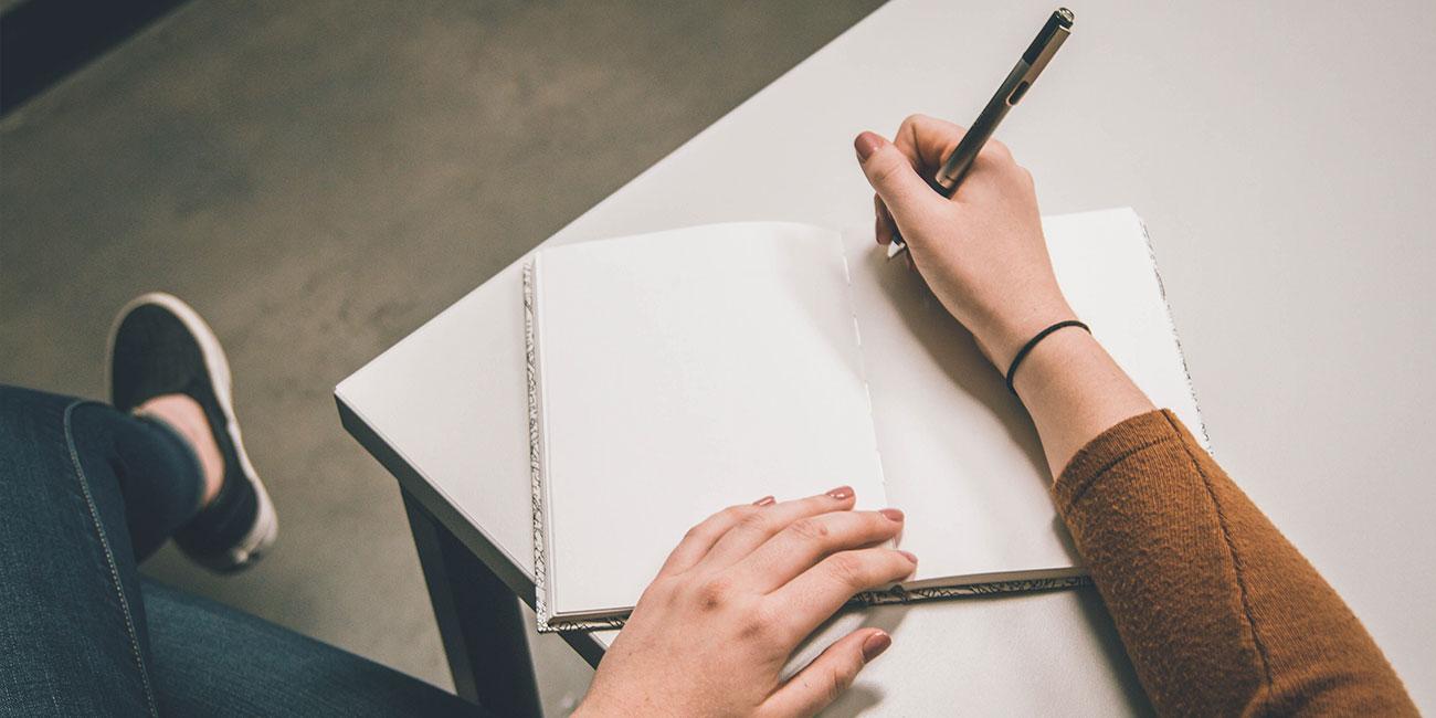 un cuaderno abierto en blanco y una mano con un bolígrafo se dispone a escribir algo.