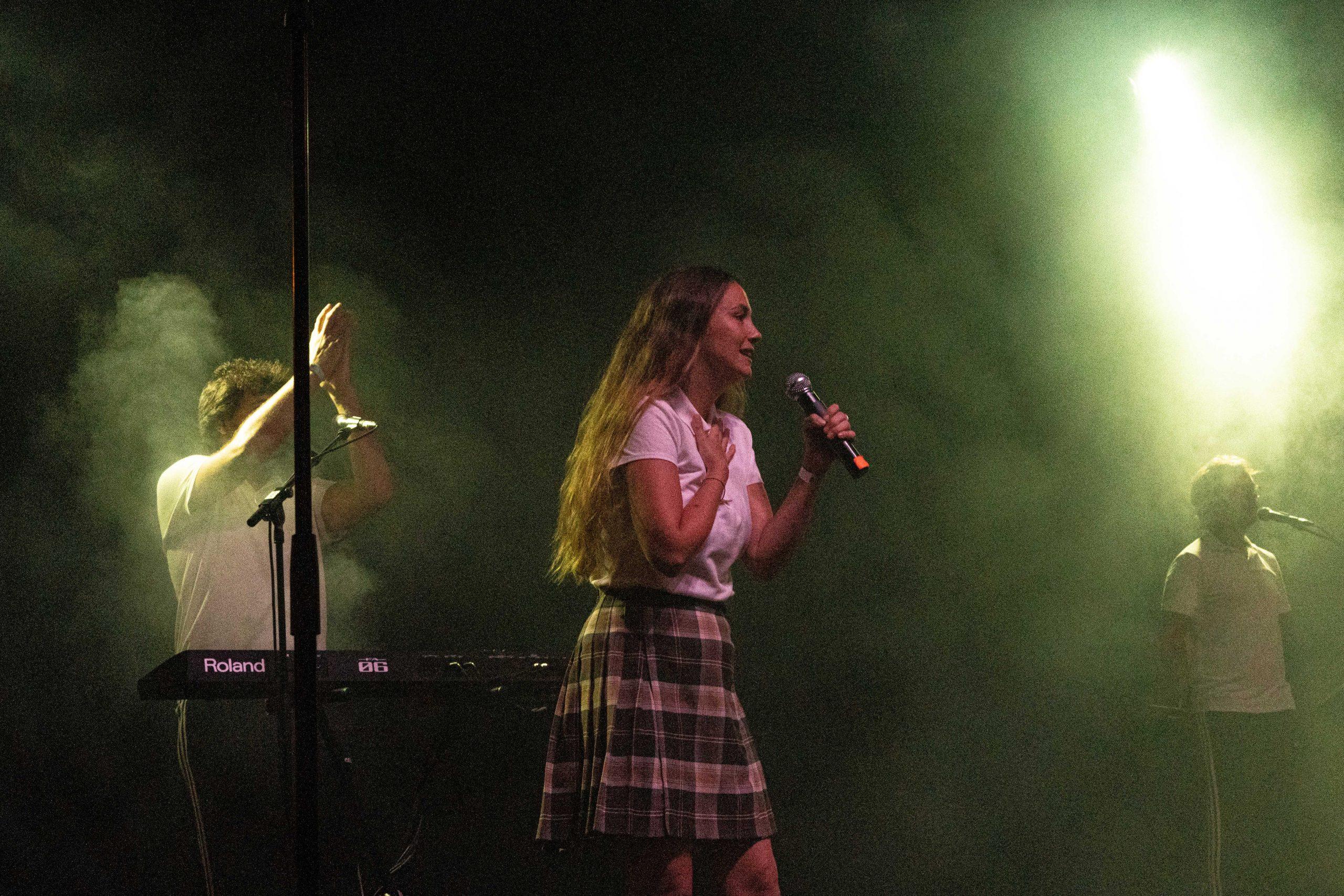 Rigoberta Bandini cantando con el micrófono y de fondo miembros de la banda durante su actuación en Pamplona.